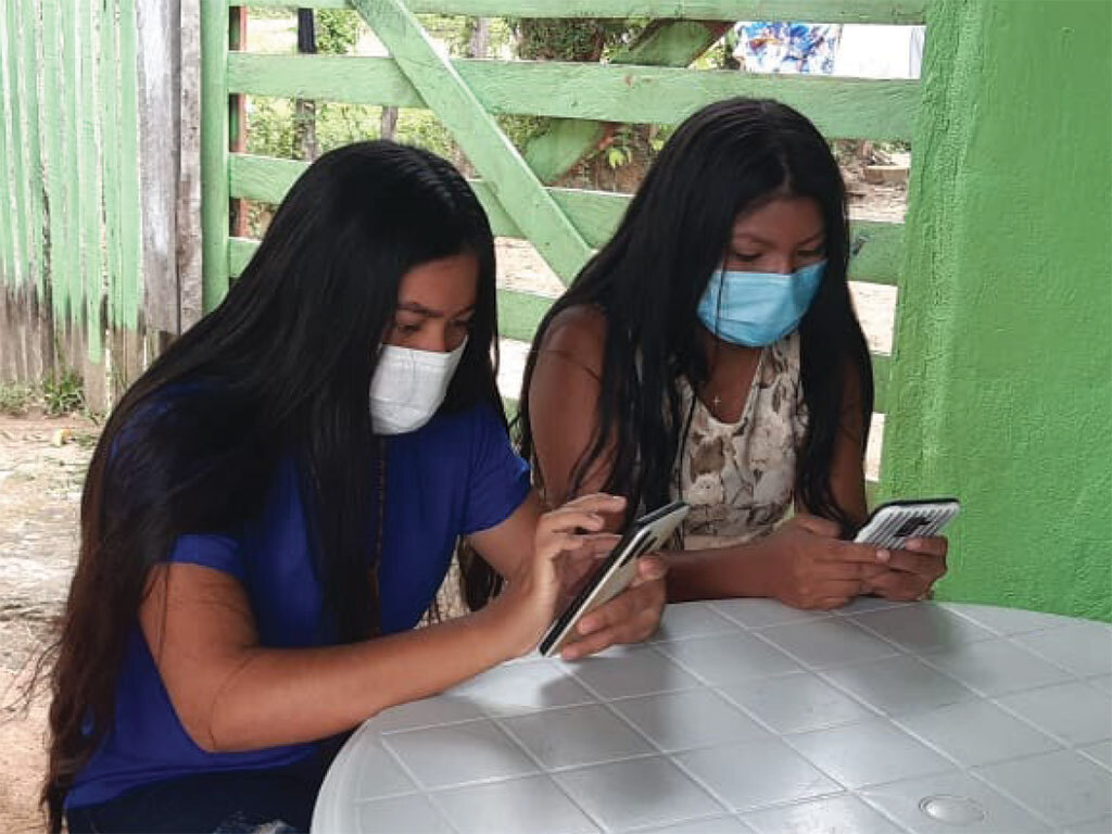Jovens da etnia Wapichana, da Comunidade Indígena Manoa-Pium (RR), respondem ao questionário em celulares.